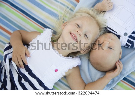 Cute Little Sister Laying Next to Her Baby Brother on Blanket.