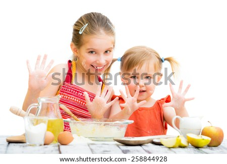 cute little sisters baking on kitchen and shows hands, on a white background - stock photo