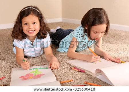 Cute little sisters coloring together - stock photo