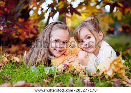 Cute little sisters hugging and kissing in autumn park - stock photo