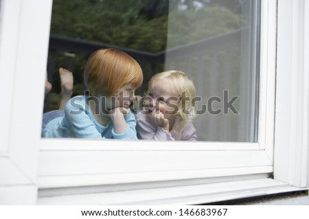 Cute little sisters looking at each other while lying in front of glass window at home