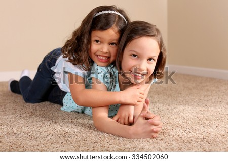 Cute little sisters lying on the carpet - stock photo