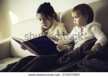 Cute little sisters reading a children book in the bed