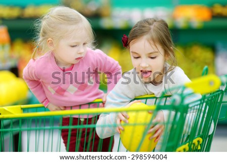 Cute little sisters shopping in a food store or a supermarket