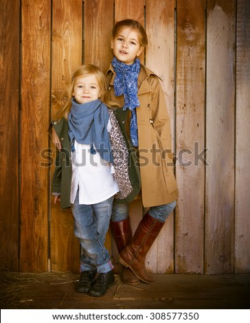 Cute little sisters wearing autumn  clothes posing over wooden background - stock photo