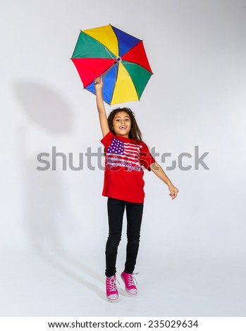 Cute little smiling afro-american girl jumping with colorful umbrella isolated on white - stock photo