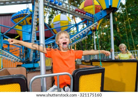 Cute little smiling boy riding a Carnival Carousel at summer theme park - stock photo