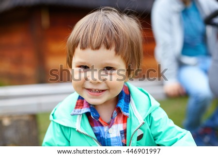 Cute little smiling toddler boy in green jacket and colored checkered shirt playing in summer park, child having fun on fresh green grass. Happy childhood, family weekend, holidays