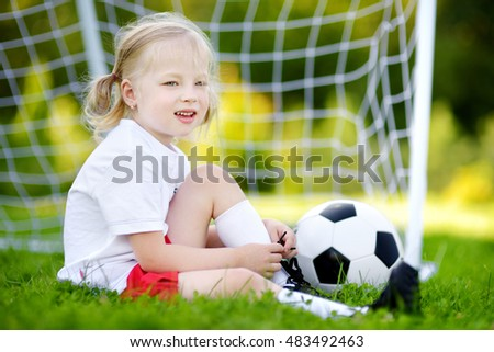 Cute little soccer player having fun playing a soccer game on sunny summer day
