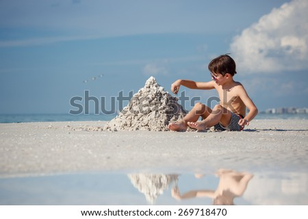 Cute little son building sand castle at beach on Florida summer holiday vacation