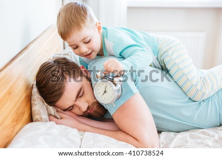 Cute little son holding alarm clock near sleeping father ear at home - stock photo