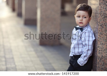 cute little stylish boy in classic style in the city - stock photo