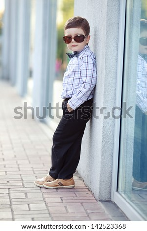 cute little stylish boy in classic style in the city in sunglasses - stock photo