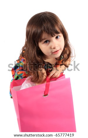 Cute little three year old girl looking to see what's in the  pink shopping back on a white background - stock photo