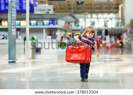 Cute little tired kid boy at the airport, traveling. Upset child waiting with big suitcase. Canceled flight due to pilot strike. - stock photo