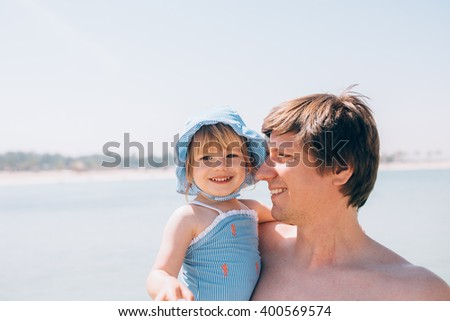 Cute little toddler baby daughter laughing with her father outdoors at the beach - stock photo
