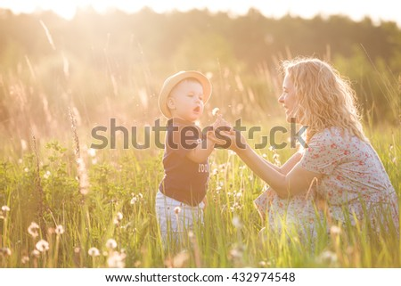 Cute little toddler boy in a straw hat holding his mother's hand and blowing dandelion. Adorable child walking with his mom in park on sunny summer day. Family on sunset. Childhood, motherhood concept - stock photo