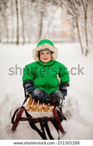 cute little toddler boy in beautiful warm outfit playing outdoors in the snow - stock photo