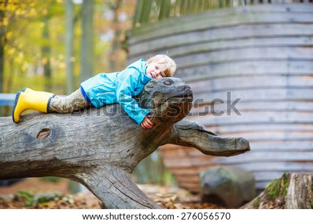 Cute little toddler boy in blue rain jacket and gumboots having fun with playing on playground on warm, autumn day, outdoors - stock photo