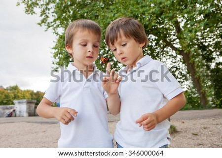 Cute little toddler boys, brothers, playing with butterfly outdoor in the park, summertime - stock photo