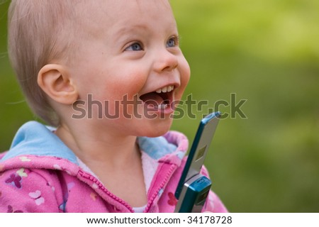 Cute little toddler girl is excited about using her mom's newer technology cell phone. - stock photo