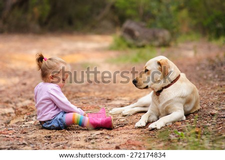 Cute little toddler girl playing with her dog labrador in a park on a warm summer day - stock photo