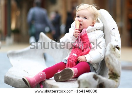Cute little toddler girl sitting outdoors in the middle of big shopping street on funny wooden chair eating ice-cream - stock photo