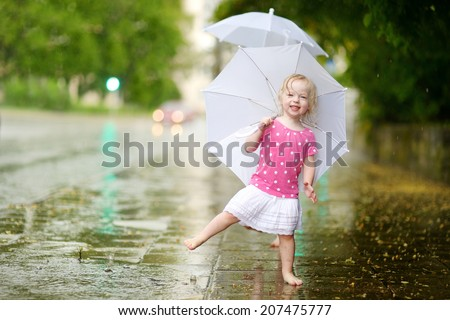 Cute little toddler girl standing in a puddle holding umbrella on a rainy summer day