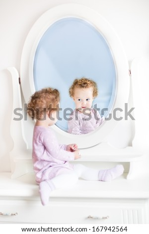 Cute little toddler girl with curly hair looking at her reflection in a beautiful white mirror - stock photo