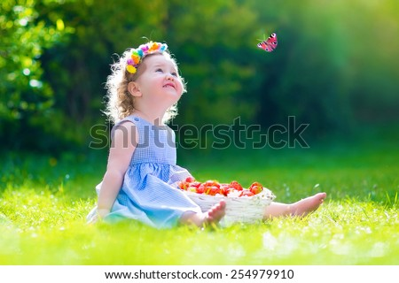 Cute little toddler girl with curly hair wearing a blue dress having fun in the garden eating healthy fresh strawberry for healthy fruit snack watching a colorful butterfly on a sunny spring day - stock photo