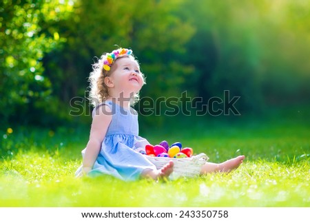Cute little toddler girl with curly hair wearing a blue summer dress having fun during Easter egg hunt relaxing in the garden on a sunny spring day - stock photo