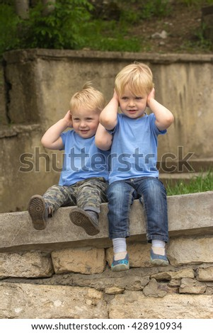 Cute little twins kid covering his ears with hands in park