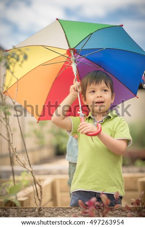 Cute little 3 year old mixed race Asian Caucasian boy plays with his rainbow umbrella outside in his suburban backyard