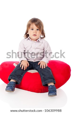 Cute little 2 years old boy wearing shirt and jeans, sitting on a heart shaped red pillow. High resolution image isolated on white background with copy space. Studio shot