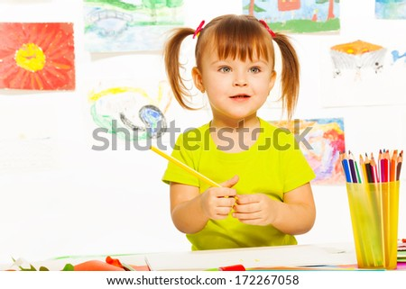 Cute little 3 years old girl in yellow shirt and pony tails holding pencil  - stock photo