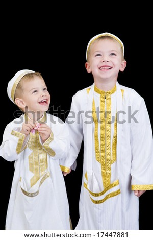 Cute little 3yr and 5yr old boys wearing traditional Arabian thobes or dishdasha for the purpose of asking for Ramadan treats. - stock photo