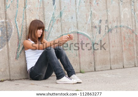 Cute lonely teenage girl sitting in urban environment.
