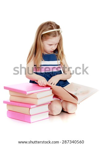 Cute long-haired Caucasian little girl reading a book sitting on the floor-isolated on white background - stock photo
