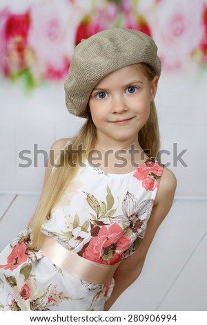 Cute long haired girl in beret tilted looks from side - children beauty and fashion concept - stock photo