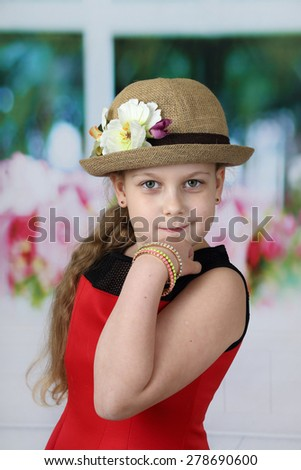 Cute long haired girl in flowers decorated hat rested her chin on fist - children beauty and fashion concept - stock photo