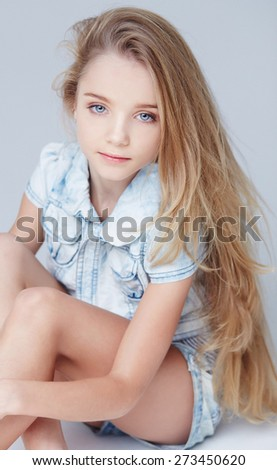 Cute long haired little girl posing in studio. Isolated on greu - stock photo