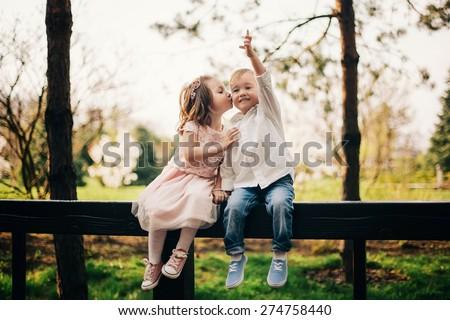 Cute love. Little girl kissing little boy outdoors in park - stock photo