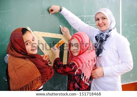 Cute lovely Arabic school children at clasroom having education activities - stock photo