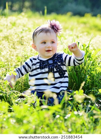 cute lovely baby in the green grass - stock photo