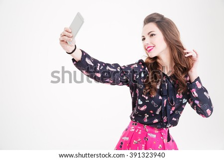Cute lovely playful young woman taking selfie with mobile phone over white background - stock photo