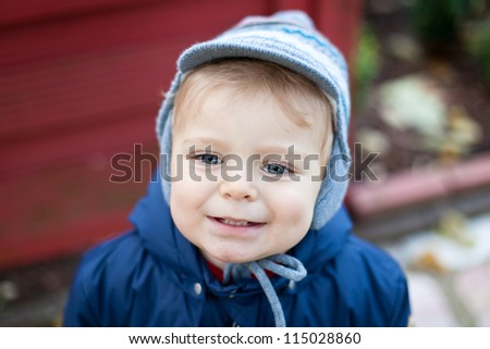 Cute lovely toddler in autumn garden in warm clothes