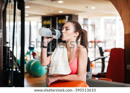 Cute lovely young woman athlete drinking water on training in gym  - stock photo