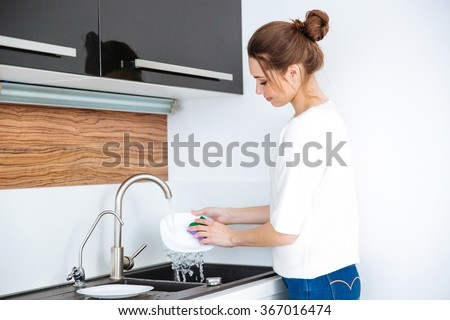 Cute lovely young woman standing and washing dishes at home - stock photo