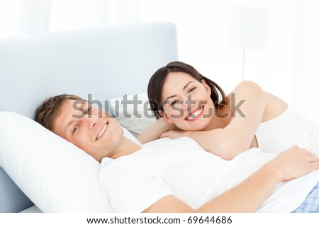 Cute lovers looking at the camera on their bed - stock photo