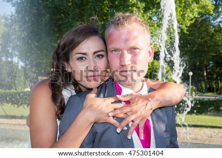 Cute loving couple standing in fountain and looking at the camera